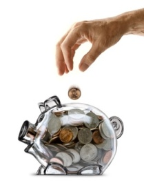 An elderly mans hand dropping a coin into a  piggy bank full of coins.
